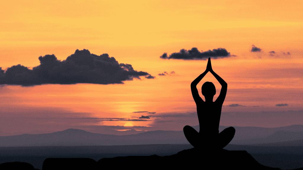 Silhueta de mulher meditando sob o pôr do sol