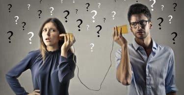 Mulher e homem seguram copos próximos de seus ouvidos: os copos estão ligados por um fio. Ao fundo, no cenário, há pontos de interrogação. Os semblantes de ambos representam confusão.