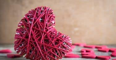 Coração rosa sobre superfície de madeira.