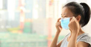 Mulher asiática colocando máscara.