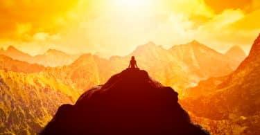 Mulher sentada no topo de uma montanha, ela está em prática meditativa. O ambiente é solar.