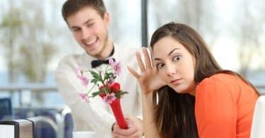 Mulher recusa homem que lhe dá flores. Ambos estão sentados à mesa.