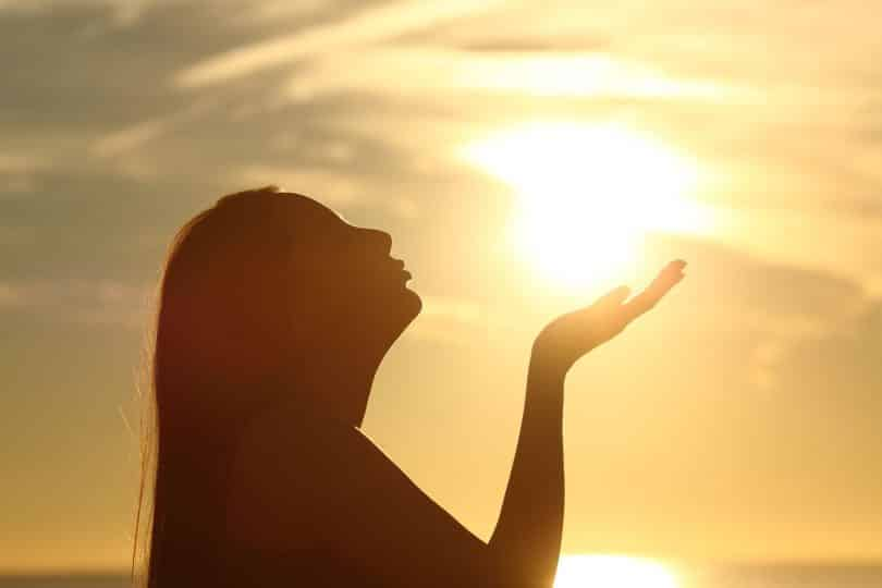 Mulher em ambiente externo ergue uma das mãos e inclina a cabeça para trás. Ao fundo, há o sol.