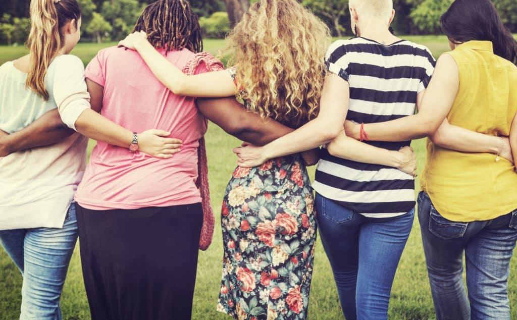 Quatro mulheres vistas de trás. Elas se abraçam.