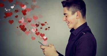 Homem mexe em celular. Deste, saem corações.
