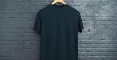 Camiseta preta em cabide pendurado em parede.