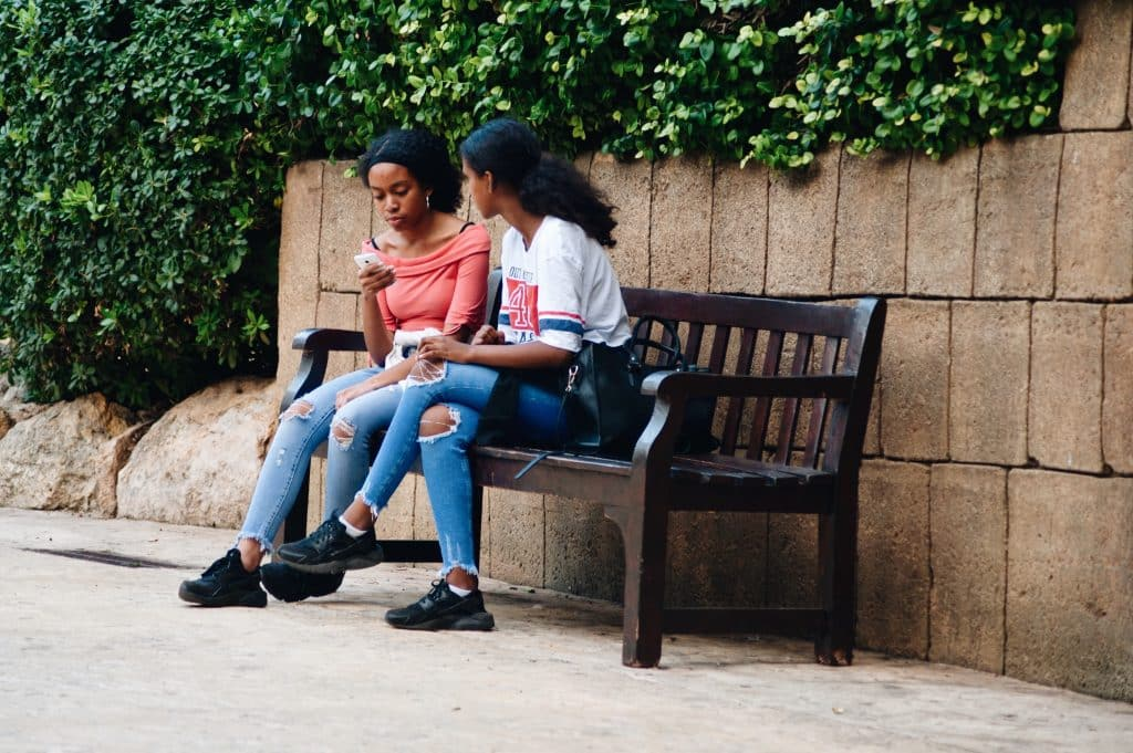 Duas jovens negras sentadas num banco conversando.