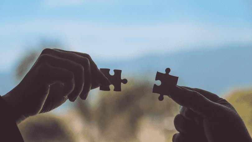 Duas pessoas encaixando duas peças de quebra-cabeça