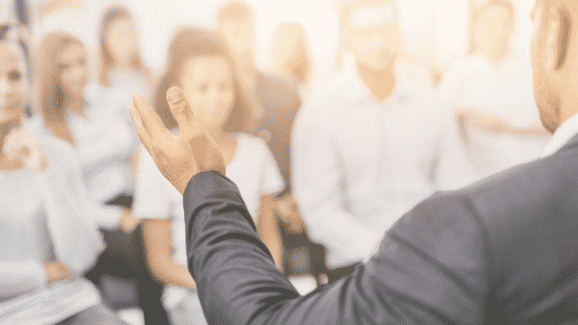 Imagem de um professor de costas ensinando seus alunos