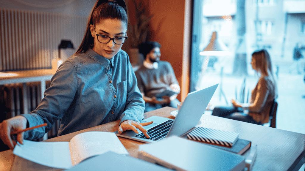 Mulher estudando em um espaço público, utilizando notebook e caderno