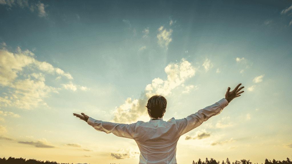 Homem com as mãos abertas em direção ao céu