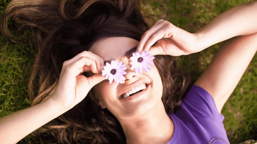 Mulher sorrindo deitada em grama com duas flores sobre os olhos