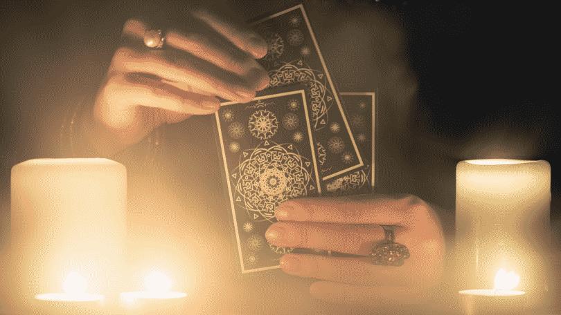 Pessoa manuseando cartas de Tarot em uma mesa. Duas velas acesas encontram-se ao lado.