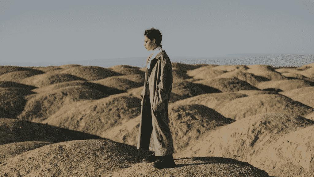 Mulher de sobretudo no meio de dunas de areia