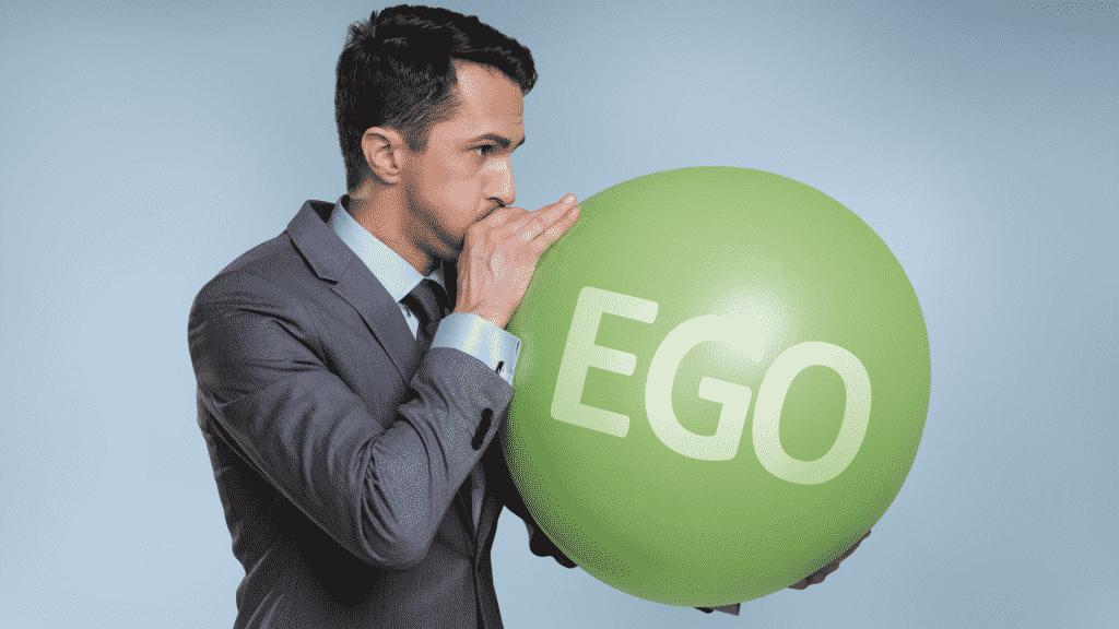 """Homem enchendo balão com a palavra """"ego"""" escrita"""