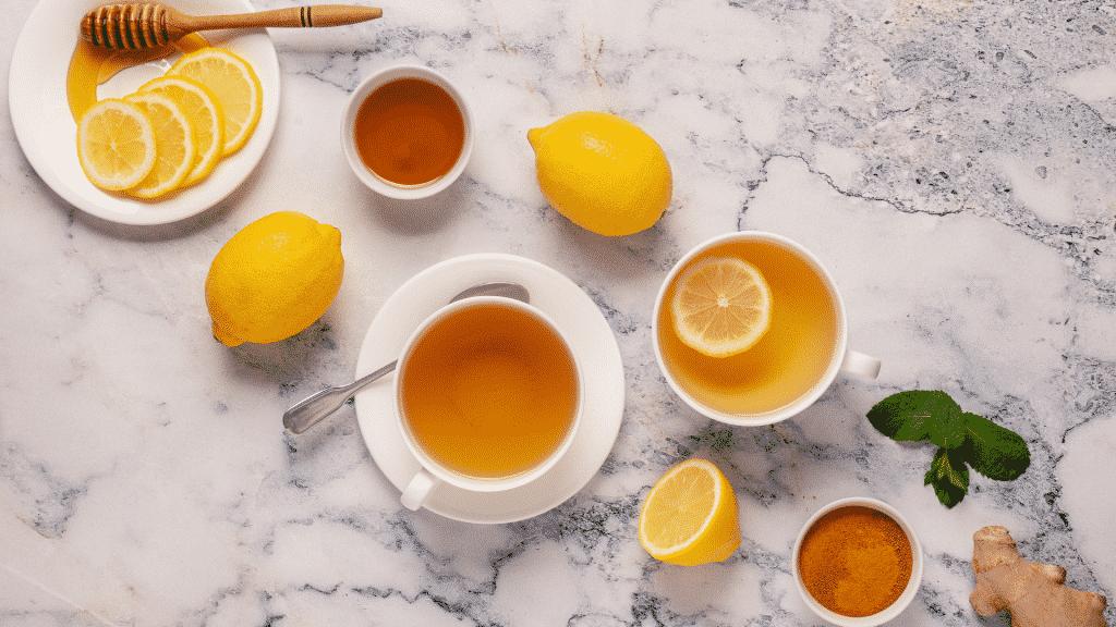 Imagem de chá de limão com mel, rodelas de limão, gengibre e hortelã, tudo em cima de uma mesa