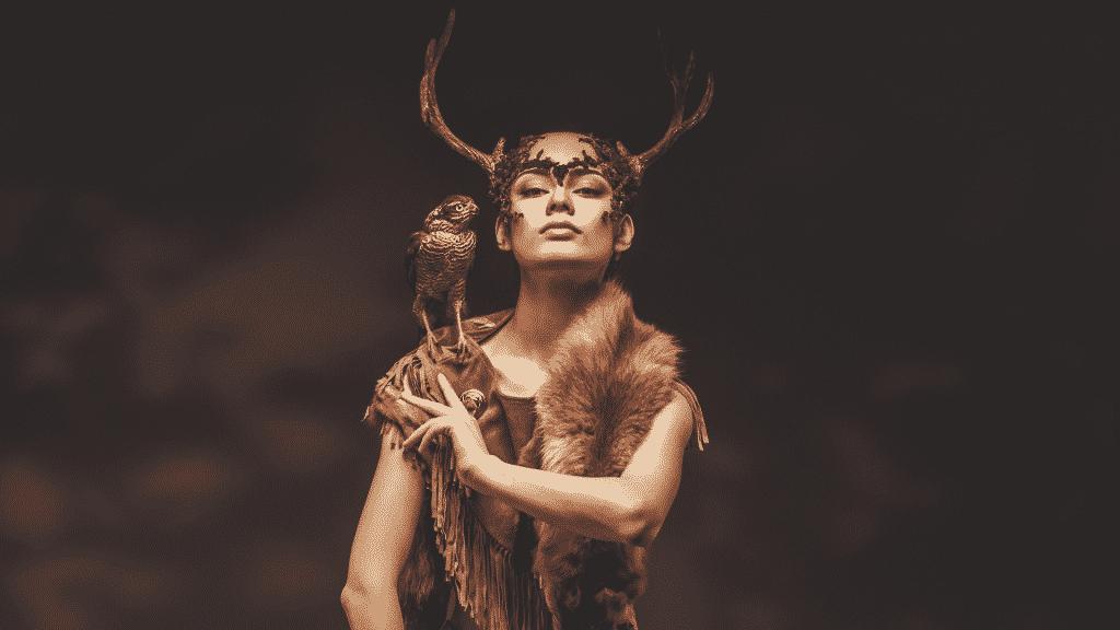 Mulher com roupas xamânicas e águia no ombro