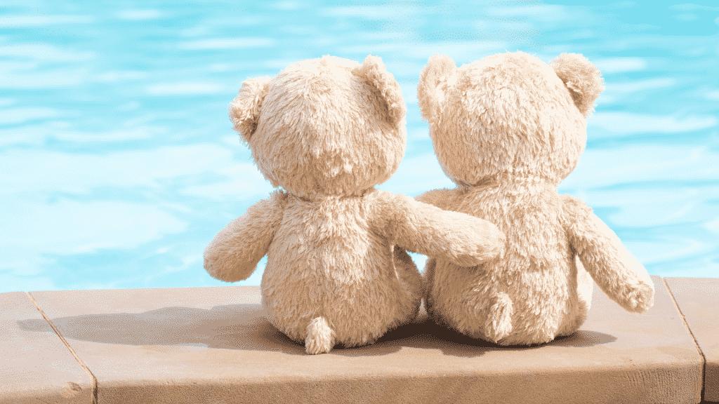 Imagem de dois ursinhos de costas, abraçados na beira da piscina