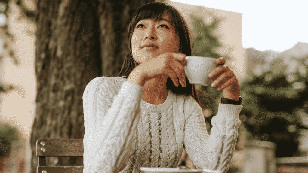 Mulher sentada tomando uma xícara de chá e refletindo