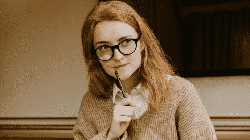 Mulher pensativa com o lápis na boca