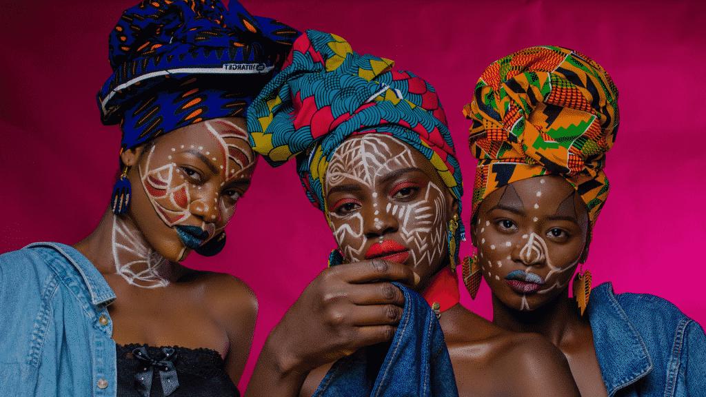 Três modelos com pinturas no rosto e usando turbantes coloridos