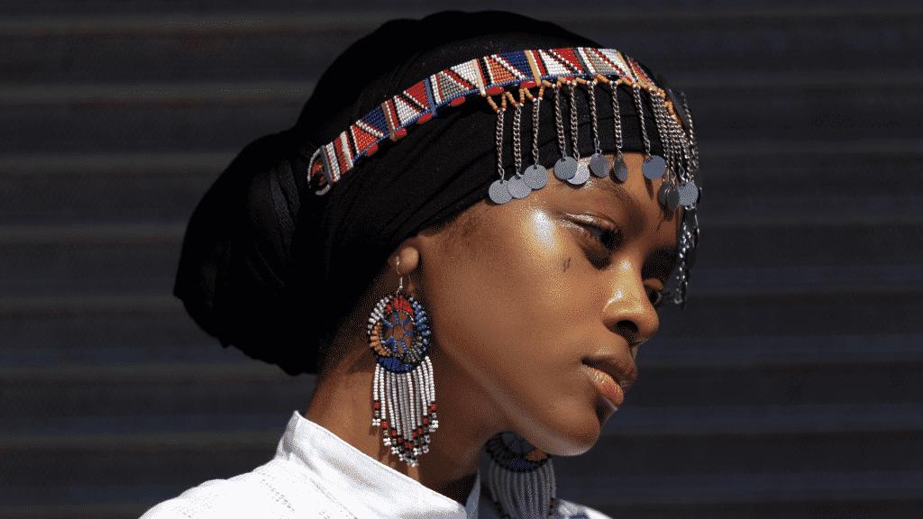 Mulher usando turbante e acessórios coloridos, em foto de perfil