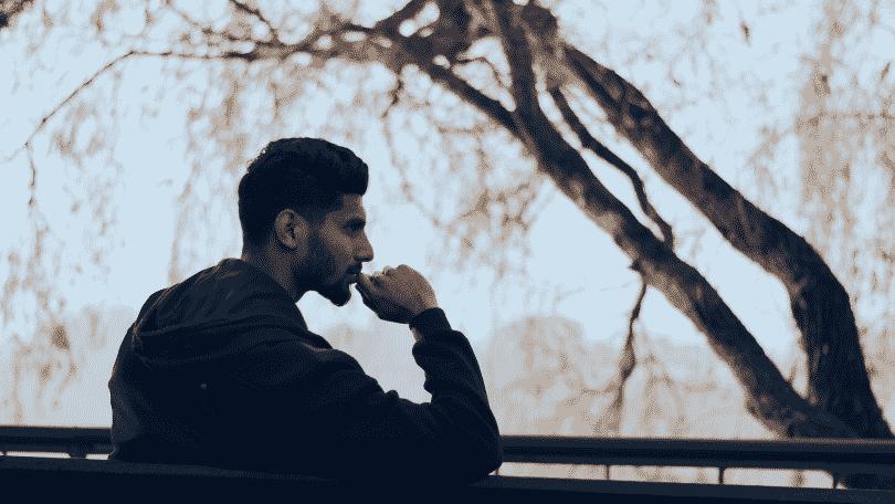 Homem sentado em um banco, pensando