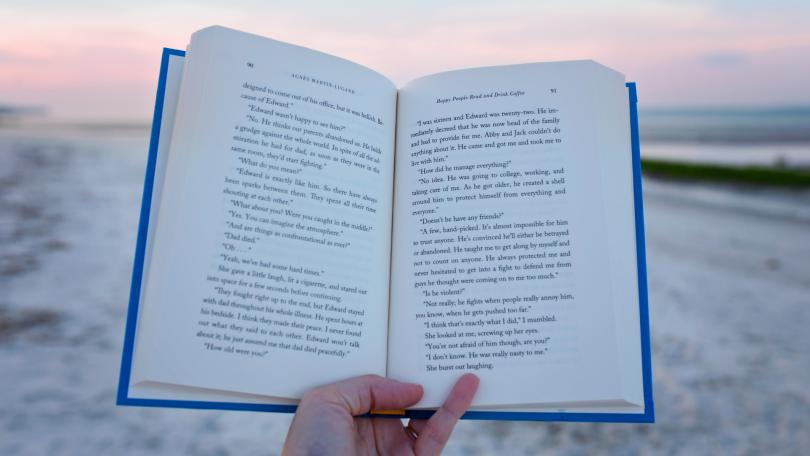 Pessoa segurando livro aberto em beira de praia