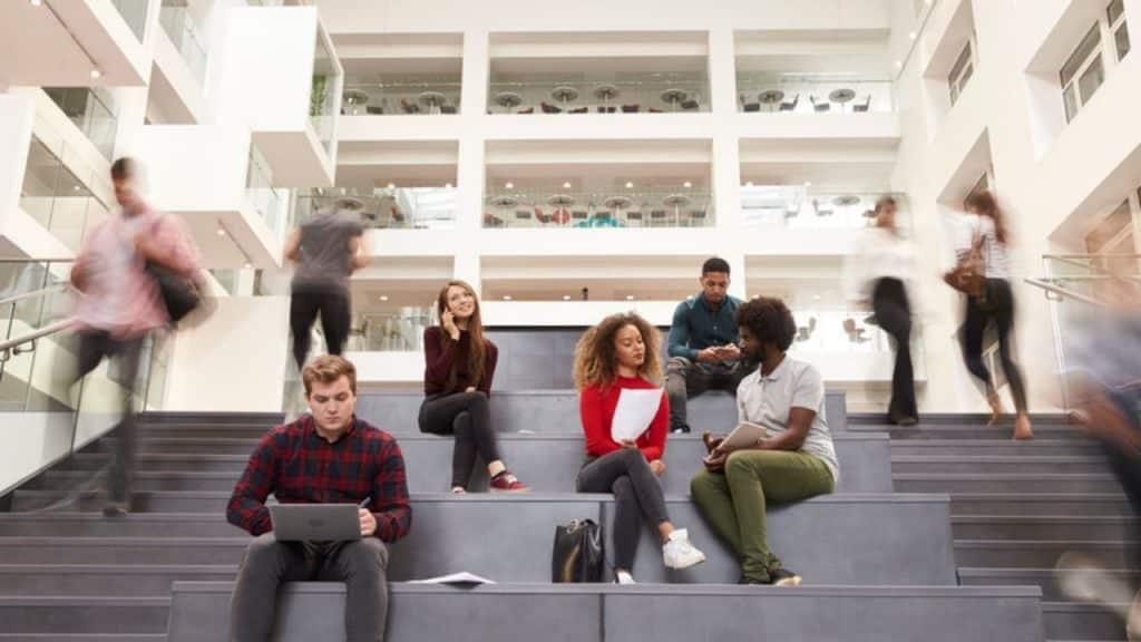 Estudantes sentados em escadaria de faculdade