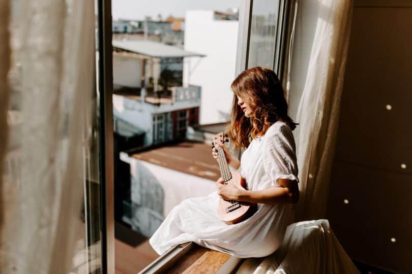 Mulher branca tocando cavaquinho na janela.