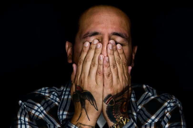 Homem branco com as mãos no rosto chorando.