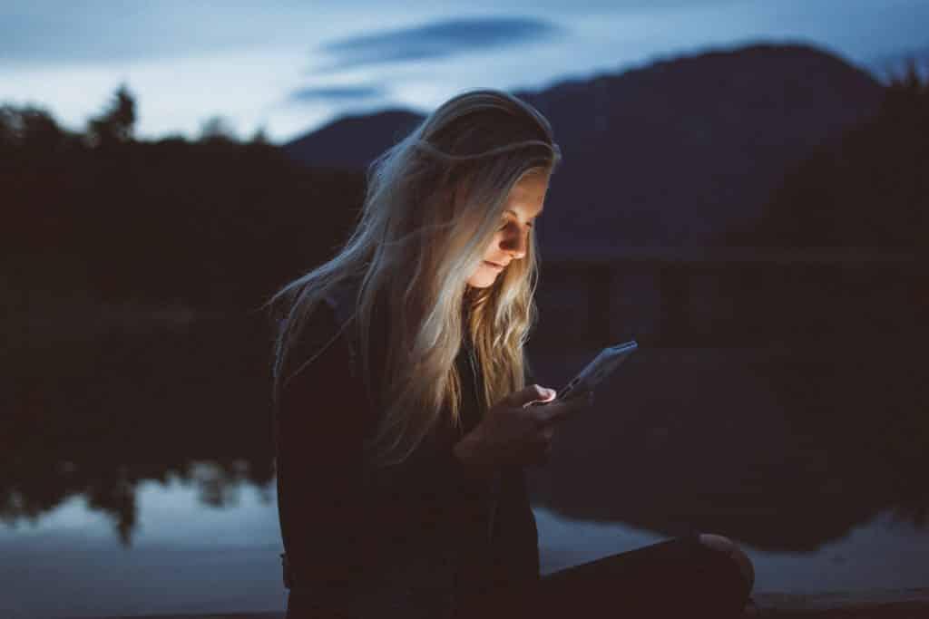Mulher branca usando o celular.