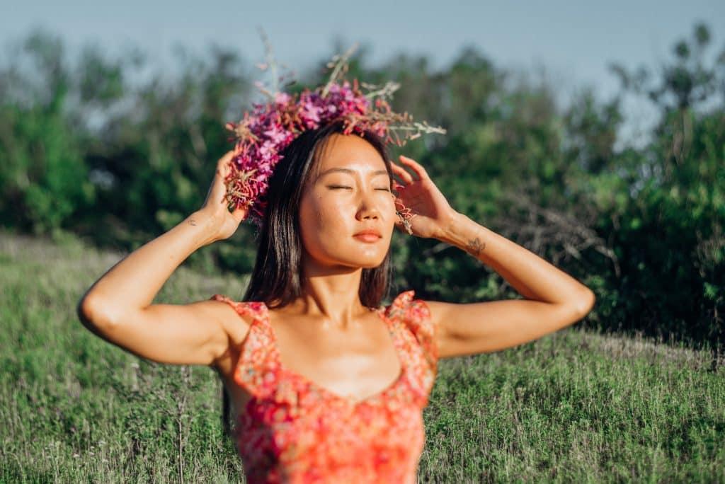 Mulher asiática sendo iluminada pelo sol com os olhos fechados.