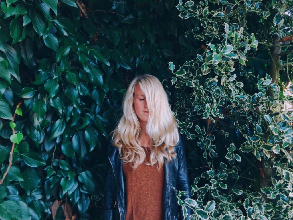 Mulher branca e loira de olhos fechados no meio de folhas.