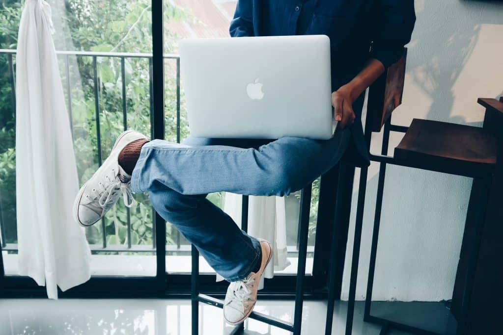 Homem negro com notebook no colo.
