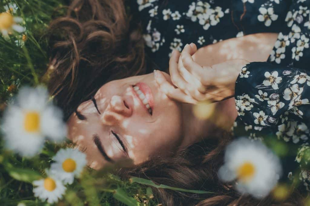 Mulher branca deitada na grama com flores brancas ao redor.