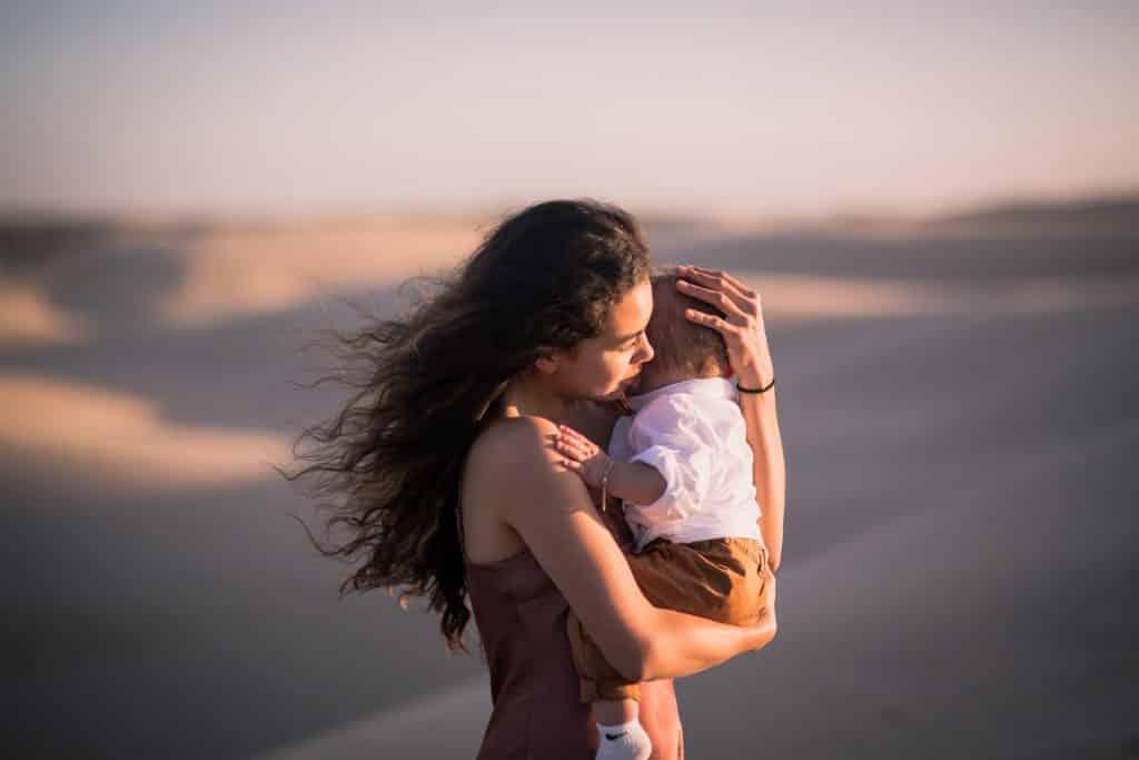 Mulher branca segurando bebê.