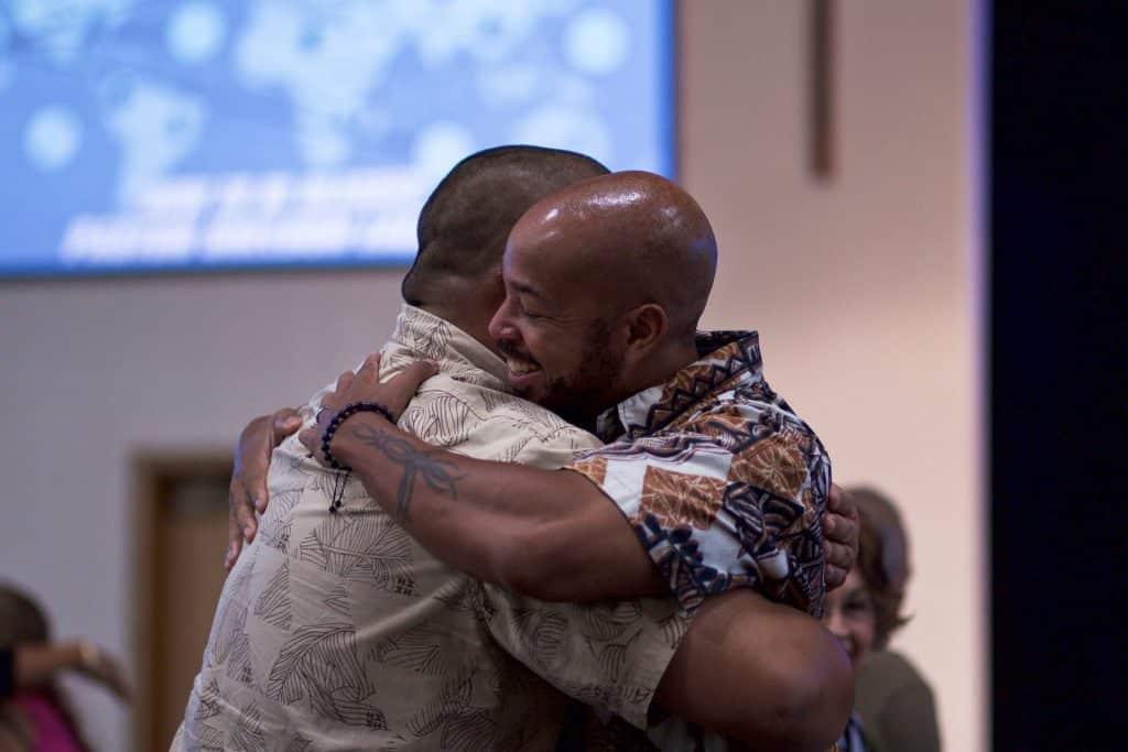 Homens negros se abraçando.
