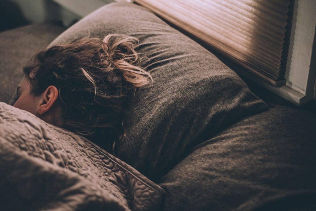 Mulher branca deitada numa cama.
