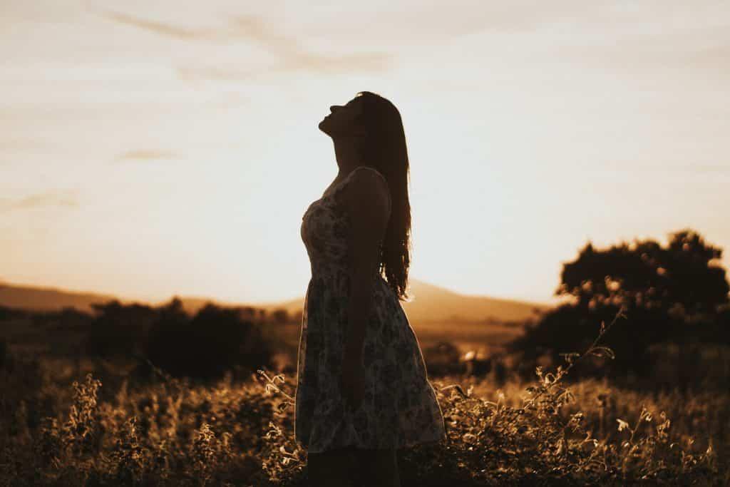 Mulher branca com os olhos fechados e cabeça levantada num campo.