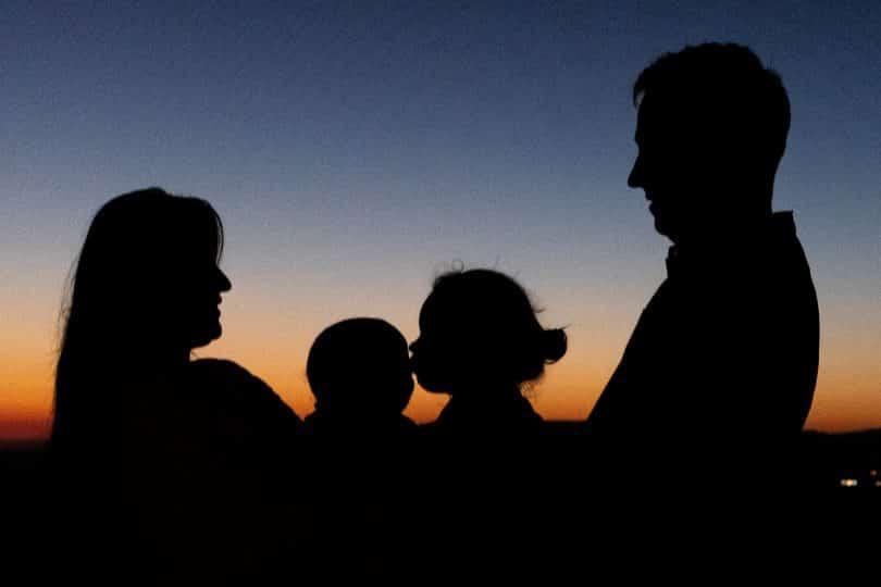 Silhueta de homem, mulher e crianças num pôr-do-sol.