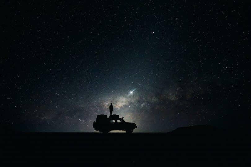 Homem em cima de um carro e o céu estrelado ao fundo.