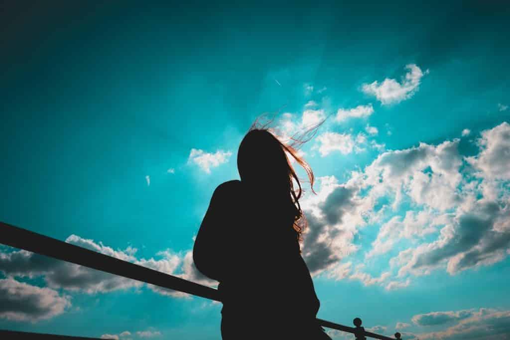 Silhueta de mulher iluminada pelo Sol.