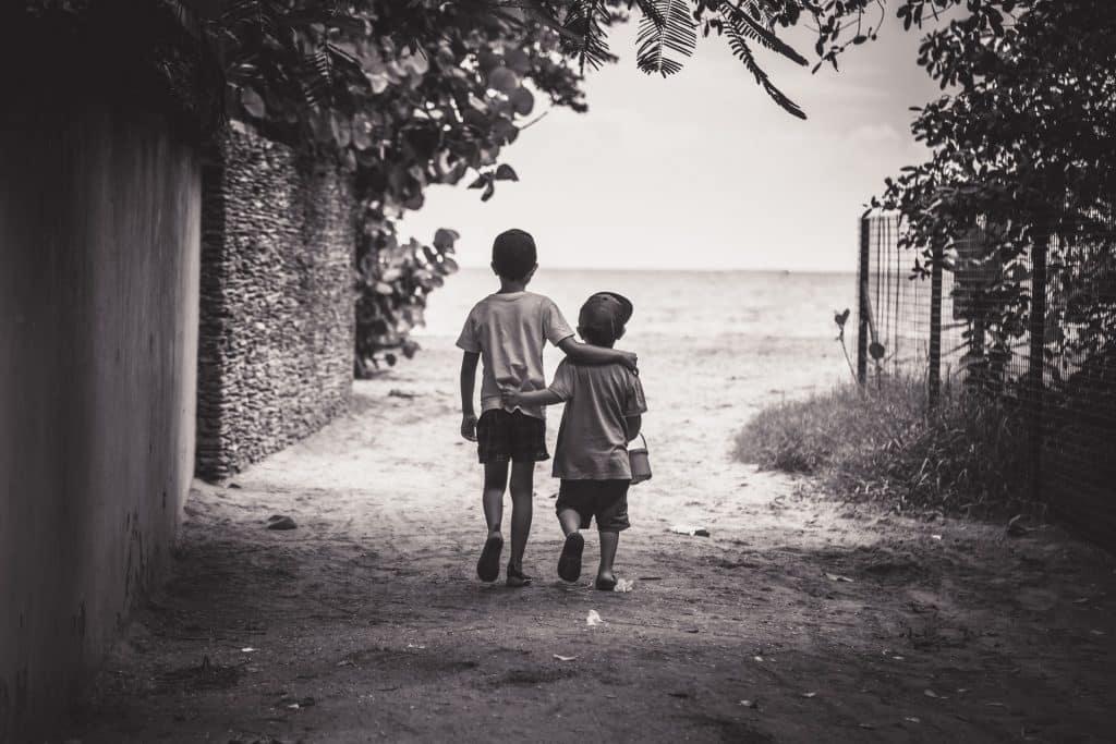 Duas crianças abraçadas a caminho da praia.