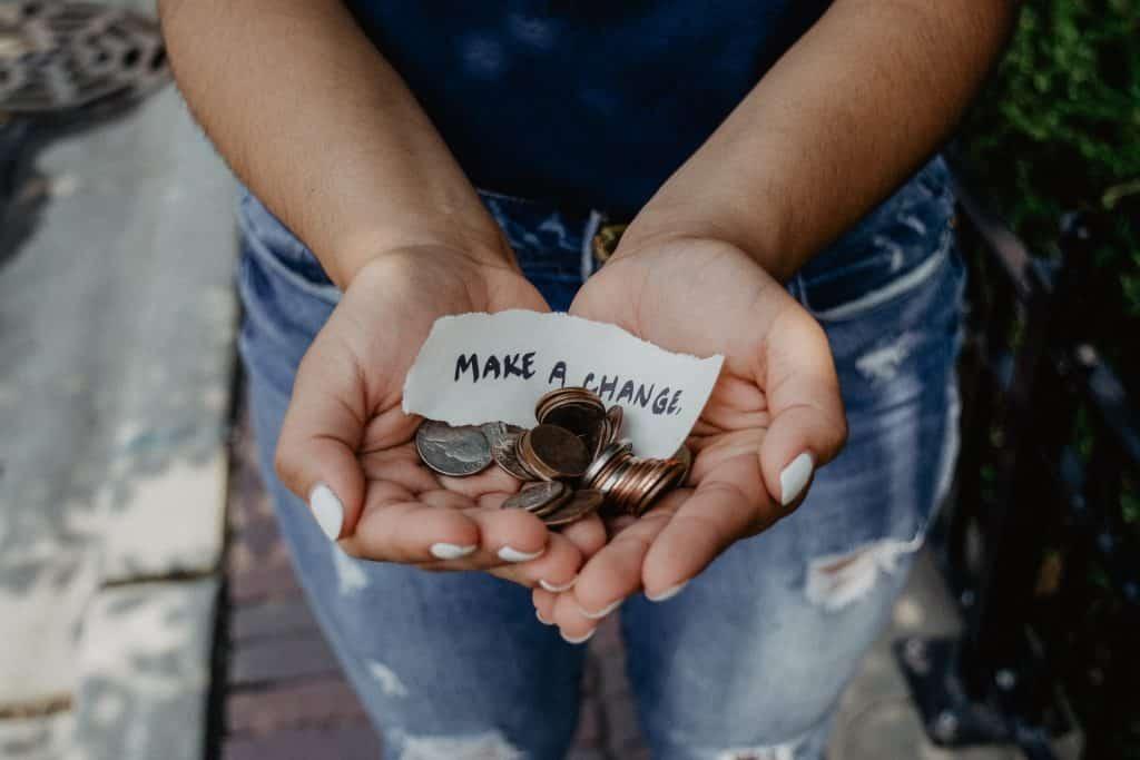 """Mulher branca segurando moedas e papel escrito """"make a change""""."""