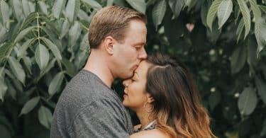 Homem branco beijando testa de mulher branca.