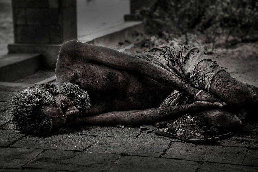 Homem sem abrigo deitado no chão e com fome