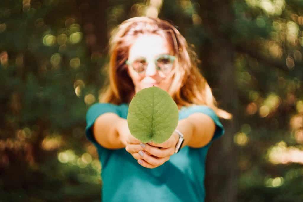 Mulher branca segurando uma folha verde.