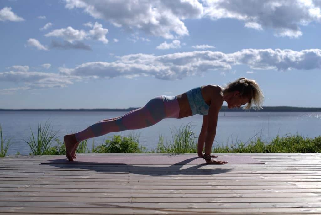 Mulher branca fazendo exercícios ao ar livre.