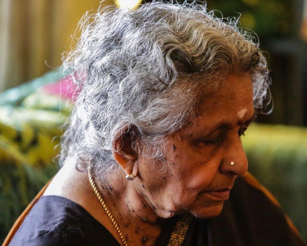 Mulher asiática com piercing no nariz e cabelos grisalhos.